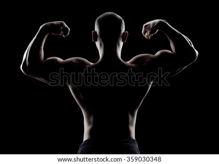 bodybuilder demonstrates biceps back view on a dark background - stock photo