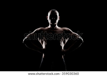 bodybuilder demonstrates biceps on a dark background