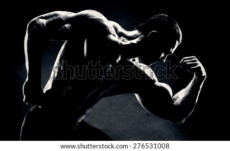 bodybuilder demonstrates biceps on a dark background is over contrast - stock photo