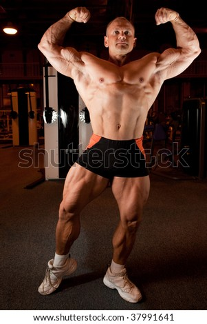 bodybuilder demonstrates his muscles - stock photo