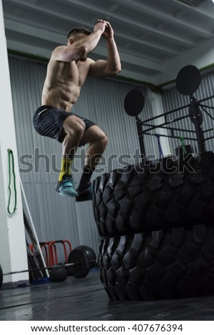 Bodybuilder doing box jumps at the gym - stock photo