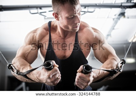 Bodybuilder doing butterfly on cable pull for better definition of his arm muscles - stock photo