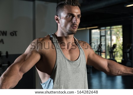 Bodybuilder Doing Exercise For Shoulder. Body Builder Workout On Cable Machine. Standing Low Pulley Deltoids Raise - stock photo