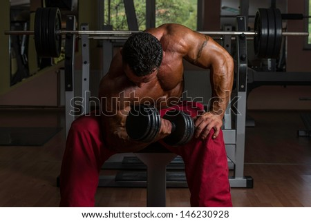 bodybuilder doing heavy weight exercise for biceps - stock photo
