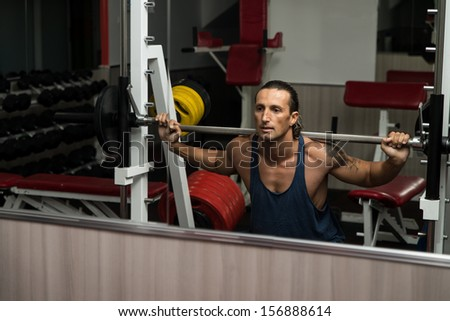 Bodybuilder Doing Squats With Barbell - stock photo