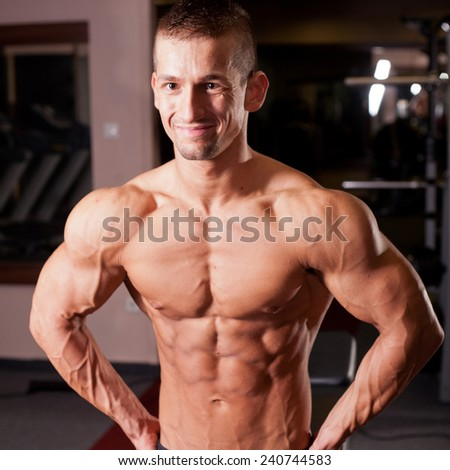 bodybuilder flexing his muscles in gym