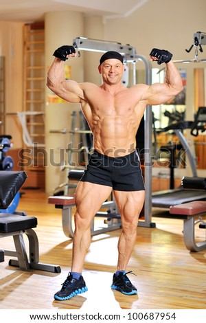 Bodybuilder flexing his muscles in gym and smiling - stock photo