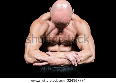 Bodybuilder flexing muscles while looking down against black background - stock photo