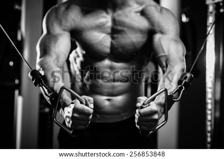 bodybuilder guy in gym pumping up hands close up. Black and white - stock photo