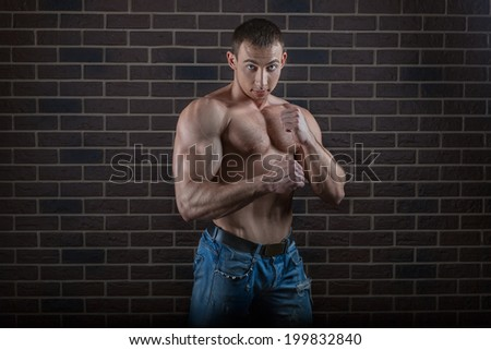 Bodybuilder guy with big muscles near brick wall in the studio.