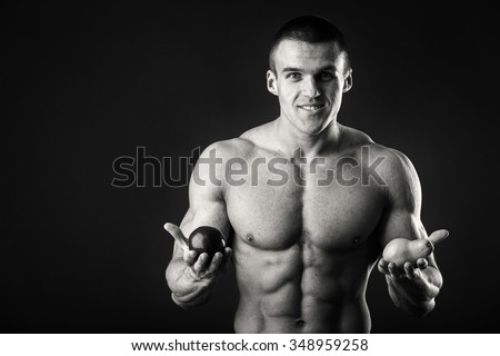 Bodybuilder holding a fruit on a dark background. Demonstration professional athlete healthy diet. Tasty and healthy, full of vitamins food. Photos for sporting and social magazines, posters.
