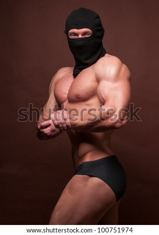Bodybuilder in a mask showing his muslces