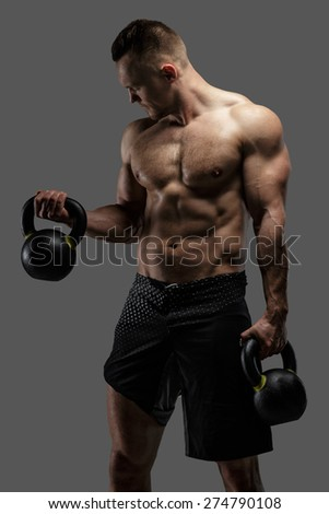 Bodybuilder in black shorts holding dumbell. Studio shoot on grey background - stock photo