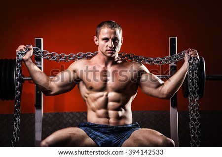 Bodybuilder in gym with iron chain.