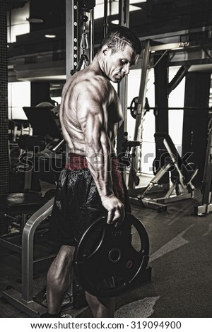 Bodybuilder in the gym. Fitness training. Advertising handsome male body. Toned image of the sportsman - stock photo