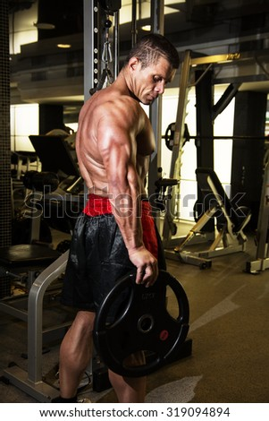 Bodybuilder in the gym. Fitness training. Advertising male body beautiful - stock photo