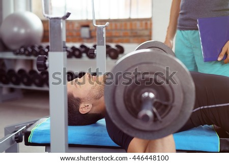 Bodybuilder lifting weights in a gym with an instructor standing by to secure the barbell once raised in a health and fitness concept - stock photo