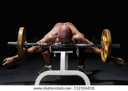 Bodybuilder lying exhausted on workout bench in gym with barbell from the back isolated on black - stock photo