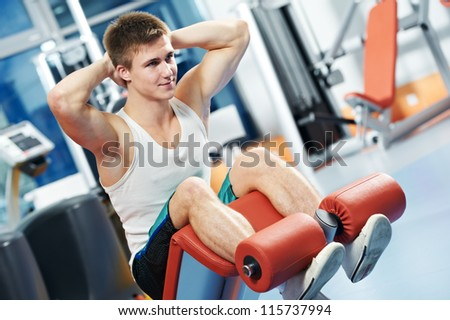 bodybuilder man at abdominal crunch muscles exercises during training in fitness gym - stock photo