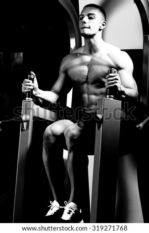 Bodybuilder man at abdominal crunch muscles exercises during training in fitness gym .Low light.
