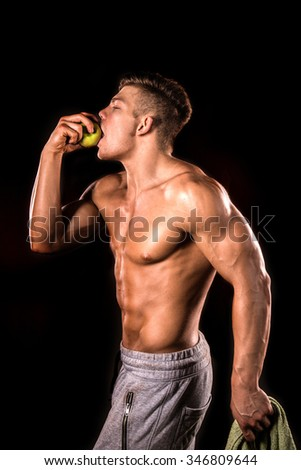 bodybuilder man  eating an apple isolated on black background
