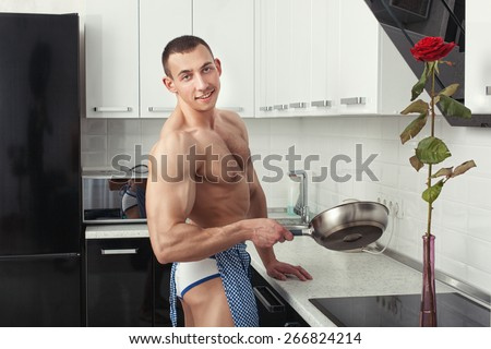 Bodybuilder man in an apron standing in the kitchen, hands holding a frying pan. - stock photo