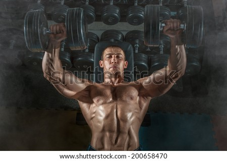 Bodybuilder man lying exercisers squeezing large dumbbells. - stock photo