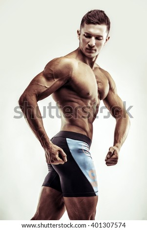 Bodybuilder man posing, showing perfect abs, houlders, biceps, triceps, chest.  - stock photo
