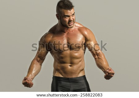 Bodybuilder man with perfect abs, shoulders,biceps, triceps and chest . Strong man flexing his muscles