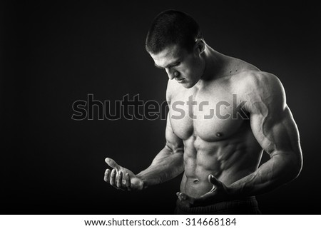 Bodybuilder on a dark background. Demonstration tense muscles. Work on your body. The success achieved exhausting work.