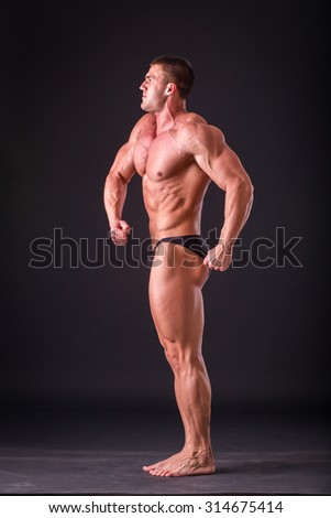 Bodybuilder on a dark background in underwear. Athlete demonstrates his muscles. The purpose and desire for success. Working on his body ended successfully. The reward for a long and exhausting work.