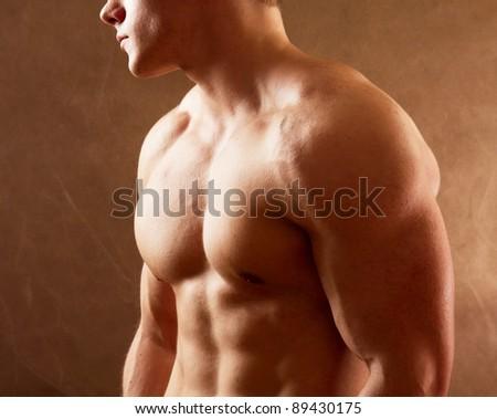 Bodybuilder on beige background - stock photo