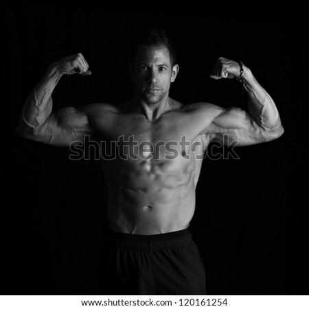 Bodybuilder on black - stock photo