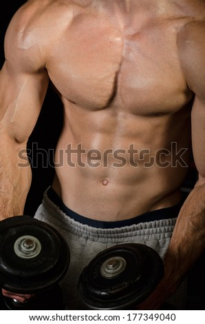 Bodybuilder Performing Bicep Curl with Dumbbell - stock photo