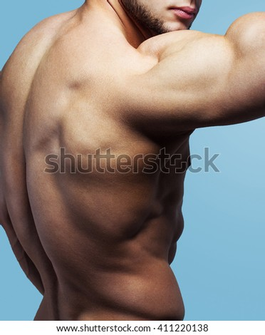 bodybuilder posing. Handsome power athletic guy male. Fitness muscular body on blue background