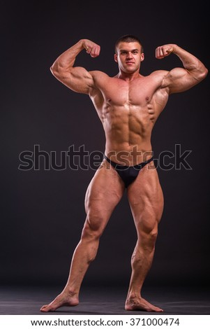 Bodybuilder posing in different poses demonstrating their muscles. Failure on a dark background. Male showing muscles straining. Beautiful muscular body athlete. - stock photo