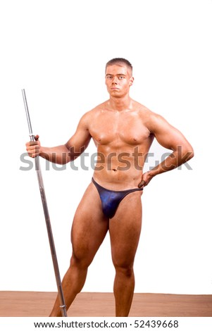 Bodybuilder posing in front of wall - stock photo