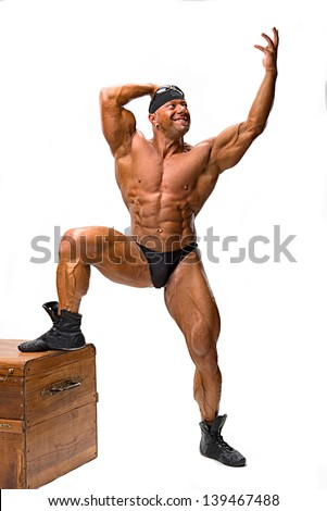 Bodybuilder posing near wooden chest on a white background - stock photo