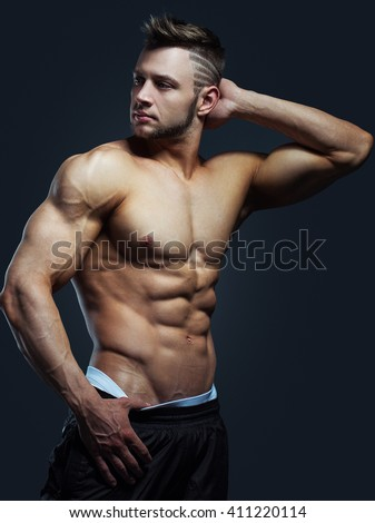 bodybuilder posing on a black background. Handsome power athletic guy male. Fitness muscular body.  - stock photo