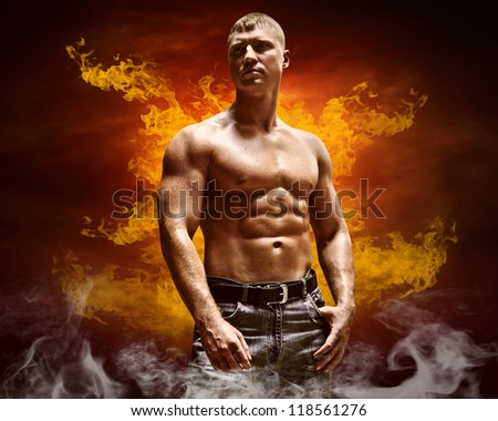 Bodybuilder posing on the fire flames background