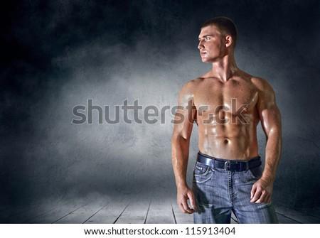 Bodybuilder posing on the outdoor grunge background - stock photo