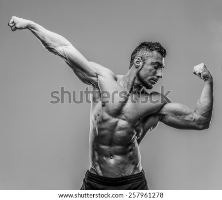 Bodybuilder posing over gray background. HDR monochrome. - stock photo