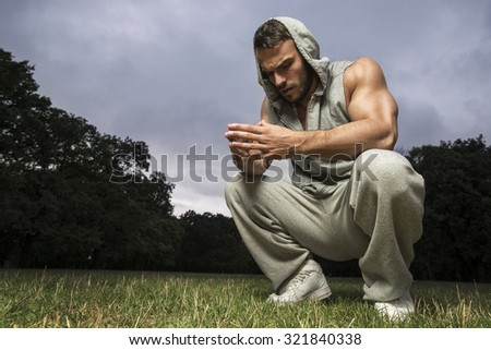 Bodybuilder resting after workout in park - stock photo