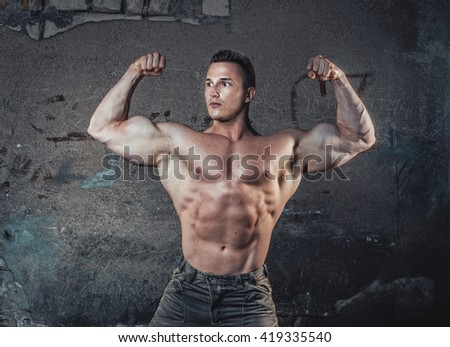 Bodybuilder showing hic biceps, young muscular man against damaged old wall