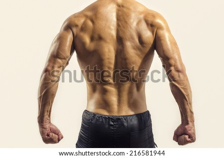 Bodybuilder showing his back and biceps muscles isolated on a white background, personal fitness trainer - stock photo