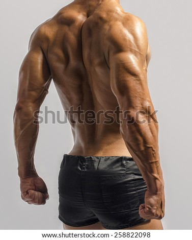 Bodybuilder showing his back and biceps muscles isolated on a white background, personal fitness trainer. Strong man flexing his muscles - stock photo