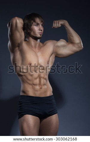 Bodybuilder showing his back and biceps muscles, personal fitness trainer.
