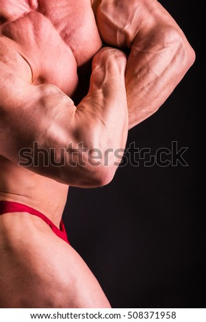Bodybuilder showing his back and biceps muscles, personal fitness trainer