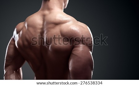 Bodybuilder showing his back and biceps muscles, personal fitness trainer. Strong man flexing his muscles - stock photo