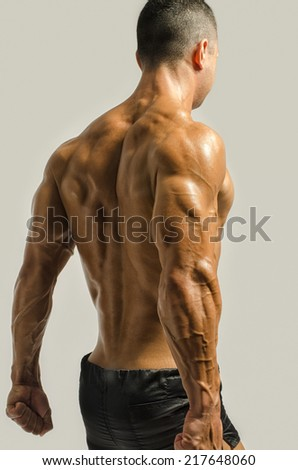 Bodybuilder showing his back,shoulders, triceps and biceps muscles, personal fitness trainer - stock photo